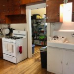 White kitchen with doorway in the center. Sink and shelves on the right and stove and counter on the left