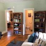 Greenish living room with walkway on the left and bathroom entrance on the right