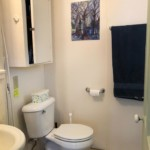 White half bathroom with painting on wall.