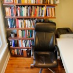 Book shelf filled with books with a black chair in front