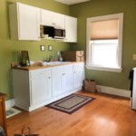 Green and white kitchen with window in the right
