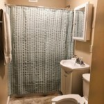 Half bathroom with sink and toilet on the right and shower in front