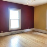 Deep red and yellow room with windows on the right and left