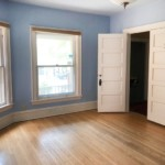Empty blue room with windows in the right and doors on left