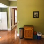 Clean green room with hallway on the left and wall in the center
