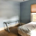 Blue room with bed, window on the right and desk on the left