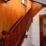 Wooden staircase with wooden door with mirror on the right