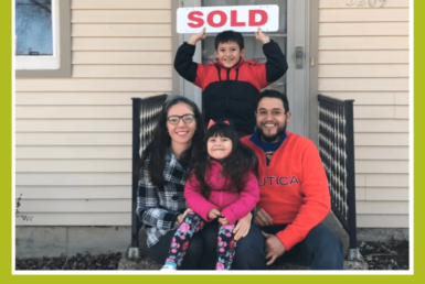 A family outside of a creme house holding a sold sign