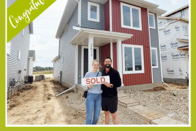 couple smiling outside of a house holding a sold sign