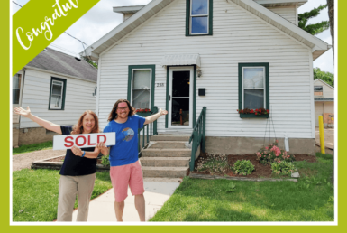 Man and woman smiling outside of a house holding a sold sign