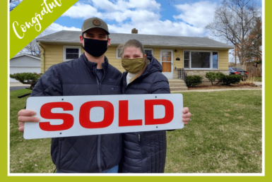 Couple smiling outside house holding a sold sign