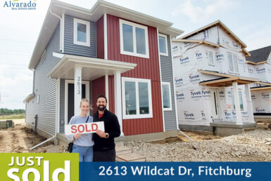 couple smiling oustide of 2 story red and gray house