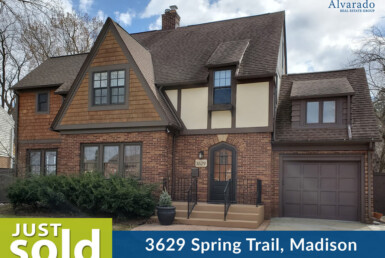 brown 2 story tudor style home with 1 car garage