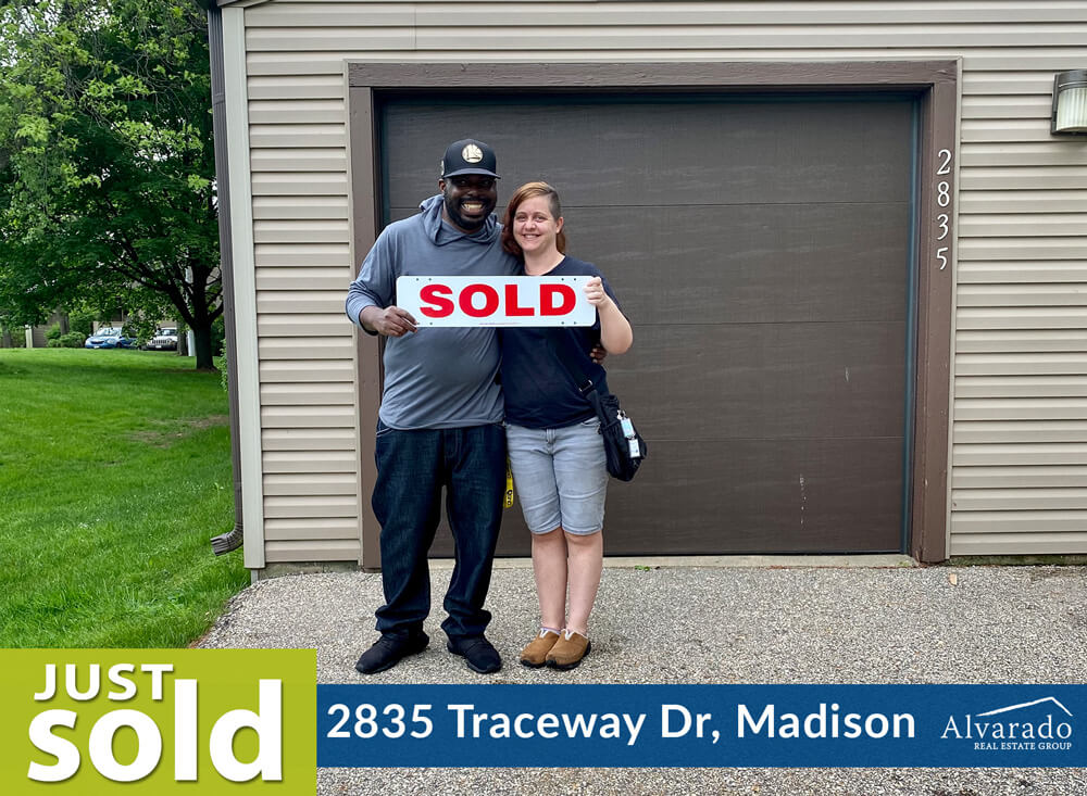 Couple smiling outside their home with a sold sign